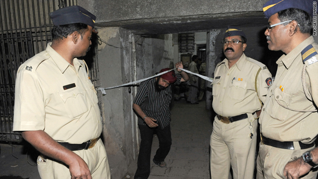 Police look on while a resident exits the building housing deceased laywer Shahid Azmi's office in Mumbai on Thursday.
