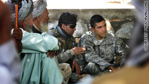Roger Hill, a former Army captain (right), meets with Afghan elders in Afghanistan with his interpreter next to him.