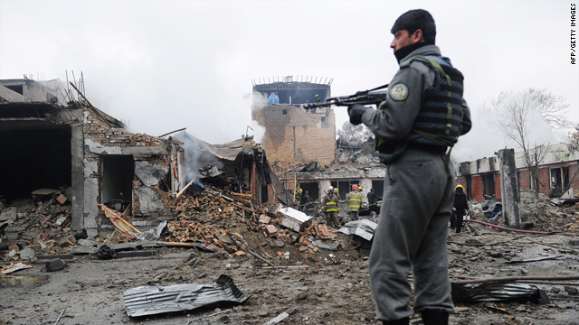An Afghan security officer stands guard as firemen inspect the debris at the site of a blast in the Shahr-E-Naw area in the  heart of the capital Kabul on Friday.