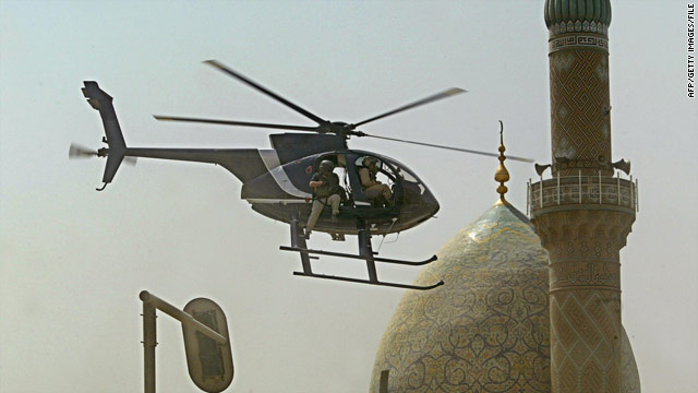 A Blackwater security firm helicopter flies low above the scene of a bomb blast near the Iranian Embassy in Baghdad in 2005.