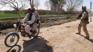 Two Afghans on a motorcycle pass a U.S. Marine in Marjah, Afghanistan, last week.