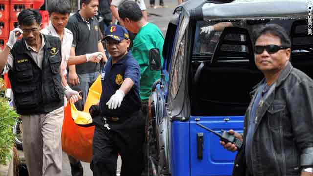 Policemen carry a body during a raid on terror suspects in Pamulang, Indonesia, on Tuesday.