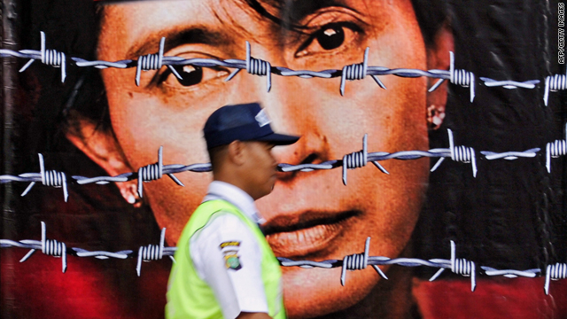 A guard passes a picture of imprisoned Aung San Suu Kyi on the front gate of the British embassy in Jakarta, Indonesia.