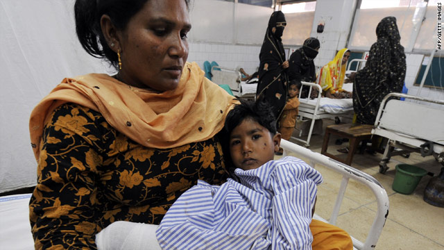 A Pakistani woman holds a boy who was injured in suicide bombings in Lahore on Friday.