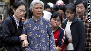Relatives grieve outside a Chinese elementary school where a man stabbed eight children to death on Tuesday.