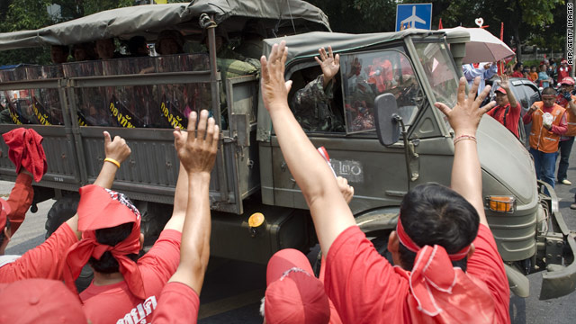 Red-shirted supporters of deposed PM Thaksin Shinawatra wave to soldiers as they leave the area in army trucks.