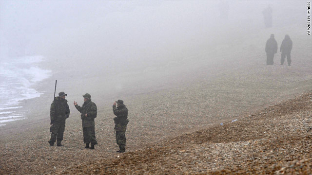 South Korean marines search the shoreline for possible survivors and bodies from the sunken warship last week.