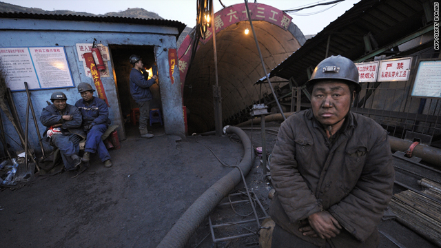 A mine worker stands outside the entrance to the Wangjialing coal mine in northern China's Shanxi province on April 5, 2010.