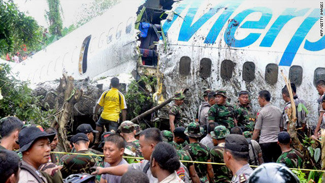 Soldiers and police examine a Merpati Airline 737 after it skidded off the runway on landing in Manokwari, Indonesia, Tuesday.