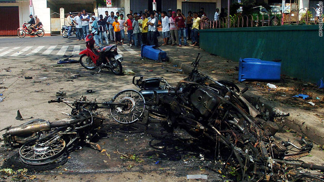 Residents look at destroyed motorbikes after bomb explosions in Isabela City, Basilan island, on Tuesday.