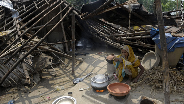 An Indian woman cooks beside her collapsed hut in the West Bengal village of Karandighi on Thursday following a storm.