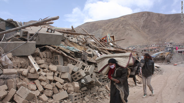 Survivors of Wednesday's earthquake move past heaps of rubble in Yushu County, China.