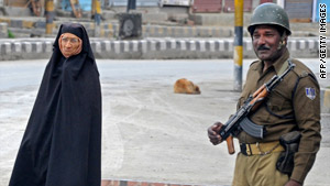 A pedestrain walks past a soldier on Friday in Srinagar.
