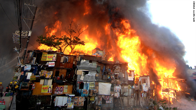 Firemen battle to control a fire raging through a shanty residential area in Quezon City, in suburban Manila, on Sunday.