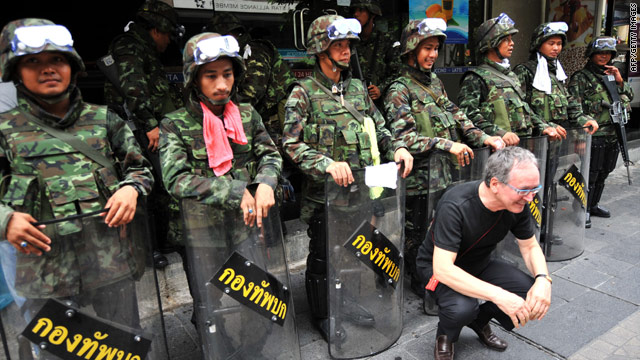 A foreign tourist poses in front of Thai soldiers near the anti-government protester camp in Bangkok on Saturday.