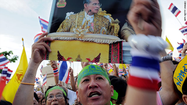 Pro-government protesters wave national flags and pictures showing Thai King Bhumibol Adulyadej in Bangkok on April 26.