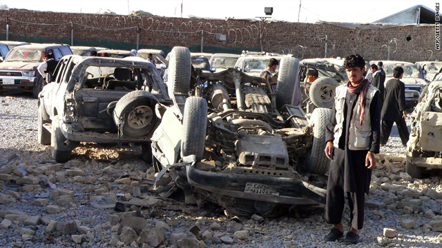 Afghans inspect the debris of a suicide bombing, including an overturned car, on the outskirts of Kandahar on April 27, 2010.