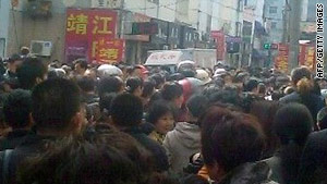 A crowd gathers outside a kindergarten in China Thursday where a man attacked more than two dozen children.