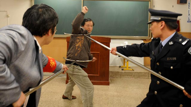Police officers show teachers and school workers at a Beijing school how to defend themselves during an attack.