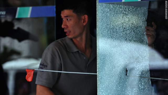 A Forensic expert inspects the site of a shooting attack at a local commercial bank's ATM booth on Silom road near to the Red Shirt anti-government protesters' fortified camp in the financial central district of Bangkok on May 8.