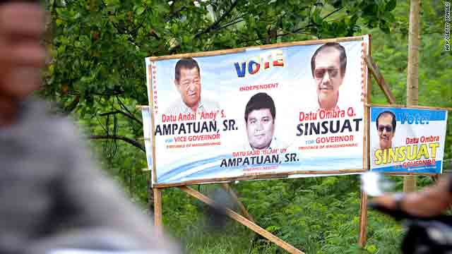 Motorcyclists in Maguindanao, Philippines, ride past a campaign poster of Andal Ampatuan Sr., who is in jail on murder charges.