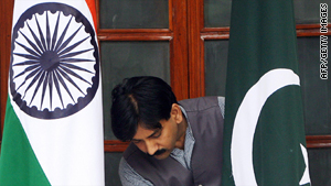 A worker adjusts the Pakistan and India flags prior to a meeting between the neighbors in 2008.