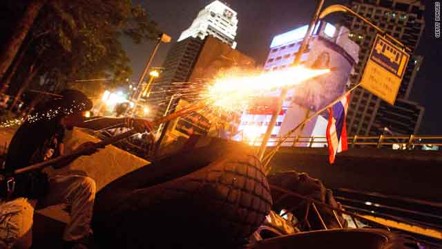 A protester fires a homemade rocket toward Thai security forces from behind barricades Thursday night in Bangkok.