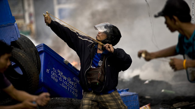 Thai demonstrators use slingshots to launch stones against security forces during clashes in Bangkok on May 16, 2010.