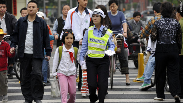 A policewoman helps a schoolgirl in Beijing on Tuesday -- China has introduced a range of measures to combat attacks on pupils.