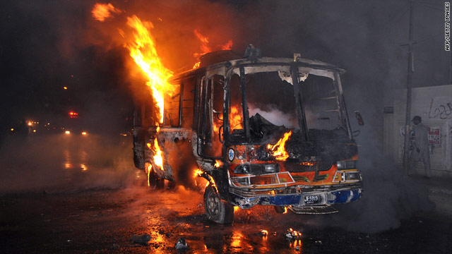 Pedestrians walk past a burning bus torched by an angry mob in Karachi on May 19.