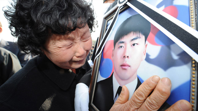 A South Korean woman weeps, holding a portrait of her son killed aboard the Cheonan, during a funeral ceremony in Daejeon on April 29, 2010.