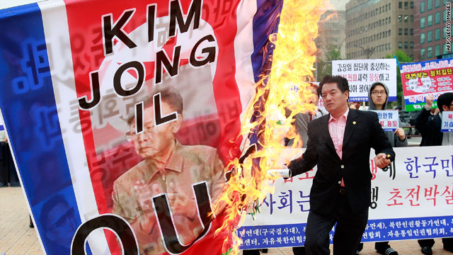 South Korean protesters burn a North Korean flag featuring a  portrait of Kim Jong-Il during a rally in Seoul on Tuesday.
