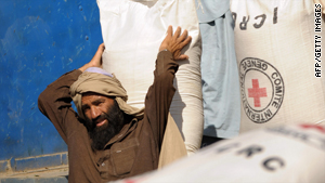 Men load foodstuffs during ICRC food distribution in Kunar province, east of Kabul on October 8, 2008.