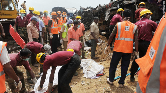Indian rescue workers remove vbodies from the site of the train wreckage.
