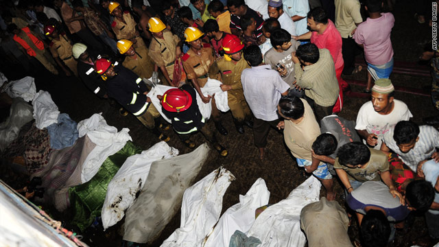 Firefighters pull victims from burned houses Thursday in Dhaka, Bangladesh.