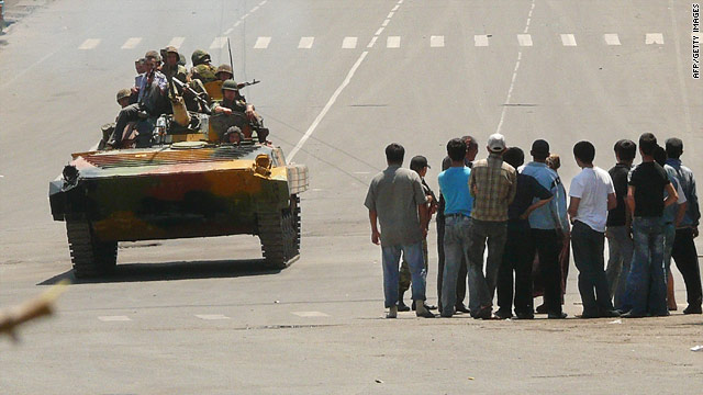 Kyrgyz soldiers on an armored vehicle drive past a group of people in Osh on June 11, 2010
