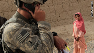 A U.S. soldier calls in coordinates near Kandahar as an Afghan girl watches earlier this month.