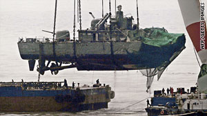 The South Korean naval ship Cheonan is lifted by a crane onto a barge in mid April, 2010.