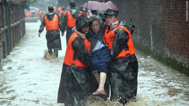 Chinese rescuers help evacuate an elderly woman as floodwaters rise in Shaowu, Fujian province.