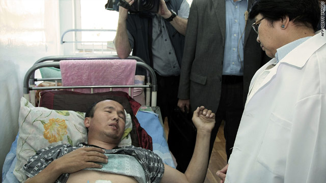 Kyrgyzstan's interim government leader Roza Otunbayeva speaks to a wounded ethnic Kyrgyz citizen in Osh on June 18, 2010.