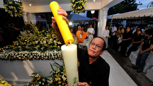 Incoming Philippines president Benigno Aquino lights a candle during a mass at his parents' tomb in Manila on Tuesday.