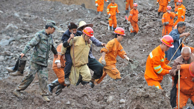Chinese rescuers help villagers evacuate from the landslide area in Guanling on June 29, 2010.
