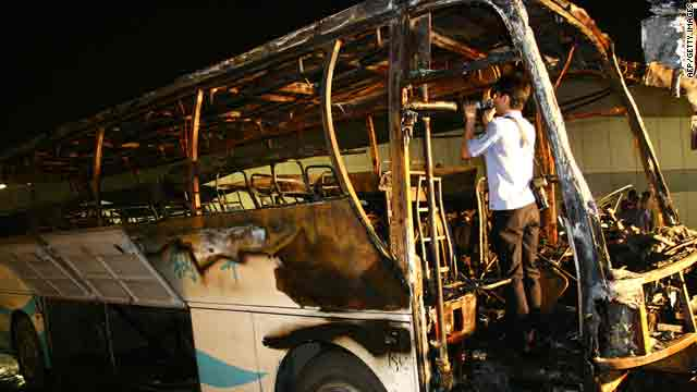 A Chinese policeman checks the burned-out bus on a road in Wuxi, China, in Jiangsu province on Monday.