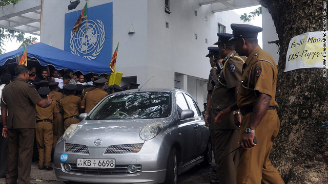 Sri Lankan police officials assist United Nations staffers exiting the UN office during a protest rally in Colombo.