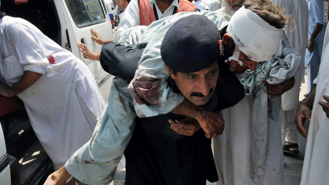 A security guard outside a hospital in Peshawar helps an injured victim of the suicide bombing on Friday.