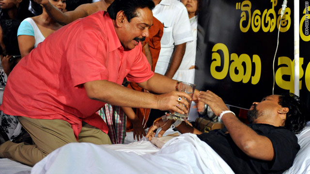 Sri Lankan President Mahinda Rajapaksa offers a glass of coconut water to fasting minister Wimal Weerawansa on July 10, 2010.