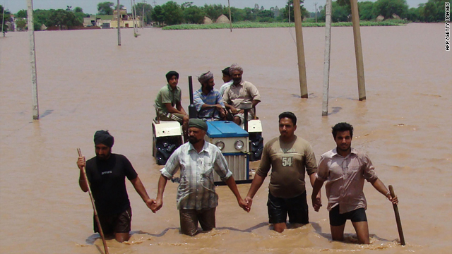 Indian village men wade and ride a tractor to safety through flood waters near Patiala in Punjab state on July 7, 2010.