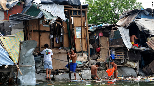 Filipinos make repairs to a shanty home after it was damaged by Tropical Storm Conson in Manila Bay on Thursday.