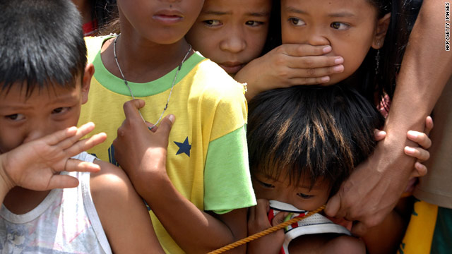 Children recoil  at the sight of a body that was recovered Friday after Typhoon Conson struck Mariveles, Philippines.