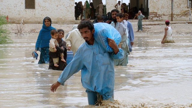 Residents carry their belongings as they evacuate flooded areas of Pakistan on Friday.